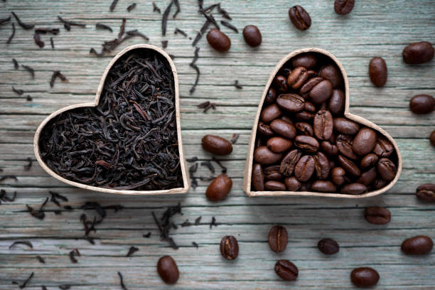 Coffee beans and black tea on a wooden background. Love coffee and tea.